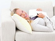 Laughing young woman lying on sofa and holding documents
