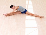 Healthy beautiful young woman stretching legs on floor