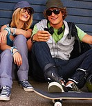 Happy young couple sitting on street looking on cellphone with skateboards