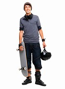Portrait of a guy standing with skateboard and helmet in hand against white background smiling