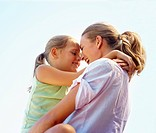 Face to face: Happy mother with her daughter with the blue sky as the background
