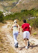 Rear view of a young couple training together out in the wilderness