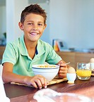 Happy boy eating a bowl a cereals for breakfast
