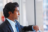 Portrait of a young Indian business man lost in thoughts