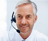 Closeup of happy mature business man working with a headset on
