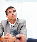 A young smart business man sitting and looking at copyspace