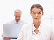Image of an attractive business woman with colleague working in the background