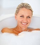 Portrait of an elegant mature woman relaxing in a bathtub