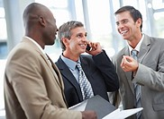 A handsome business man communicating using mobile with his colleagues standing besides