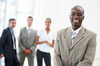Portrait of a satisfied young African American business man with coworkers standing behind