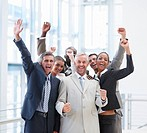 A professional group of business people smiling with their hands raised