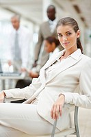 A beautiful young business woman sitting on the chair with colleagues in the background