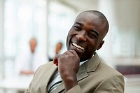 A cheerful African American business man laughing with hand on the chin