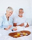 Cute old couple in bed having the morning breakfast