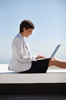 Happy business woman working on a laptop while sitting outdoors