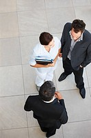 Upwards view of a business group standing and discussing business issues