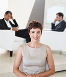 Photo of a young business woman smiling with her colleagues sitting at the back