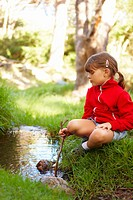 Portrait of a cute young girl sitting by the banks of a stream