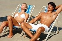 Happy young couple sunbathing on the beach