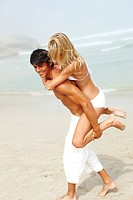 Romantic boyfriend piggybacking her cute girlfriend on the beach