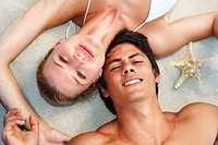Closeup portrait of a happy young woman and man lying on the sand at the beach
