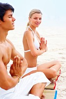 Portrait of a happy young woman sitting at the beach practicing yoga with a man beside her