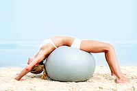 Portrait of a young woman working out on a fitness ball on the beach