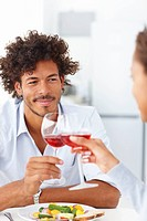 Portrait of a happy young couple on a date having red wine and a meal together
