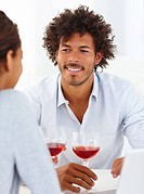 Portrait of a happy young couple having a glass of red wine together