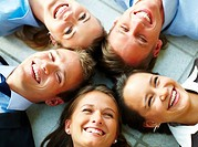 Portrait of a happy business team lying down on the floor in a circle