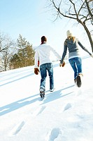 Rear view image of a young couple walking on snow