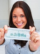 Portrait of pretty young woman showing a money note