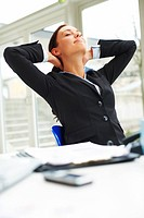 Portrait of beautiful businesswoman in black suit relaxing in the office