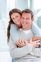 Portrait of a beautiful young woman hugging her husband from behind