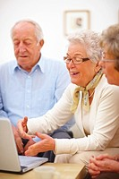 Portrait image of a group of old people discussing over a laptop