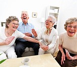A group of happy old people enjoying themselves over a card game