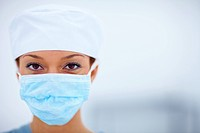 Closeup portrait of female doctor wearing surgical cap and mask