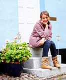 Cute smiling woman sitting on front stairs outside house