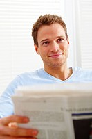 Closeup of a happy young man at home reading newspaper
