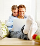 Happy romantic young couple working on a laptop in the house