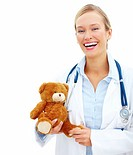 Charming young doctor holding a brown teddy bear over white background