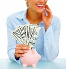 Cropped image of a young businesswoman putting cash into a piggybank isolated over white background