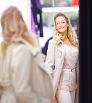 Woman trying on clothes in front of a mirror and smiling at a shopping mall