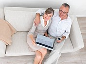 Portrait of smiling old couple sitting together on couch with laptop and coffee