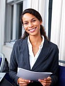 Young happy business woman standing in office holding paper in hand