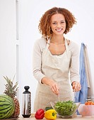 Happy young woman preparing food at kitchen