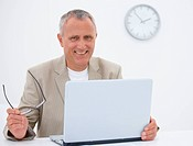 Portrait of a smiling senior business man using a laptop and holding glasses