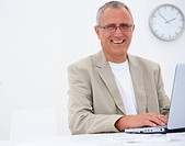 Closeup portrait of a smiling mature business man using a laptop smiling