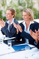 Attractive young business women applauding on an achievement at work