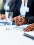 Business man making a note during a meeting, focus on the water glass